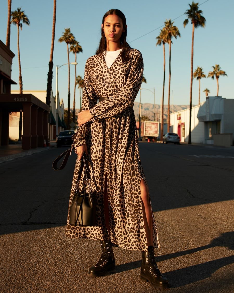 Image of a woman standing in a street in LA wearing a long leopard print silk dress with black leather boots and bag.