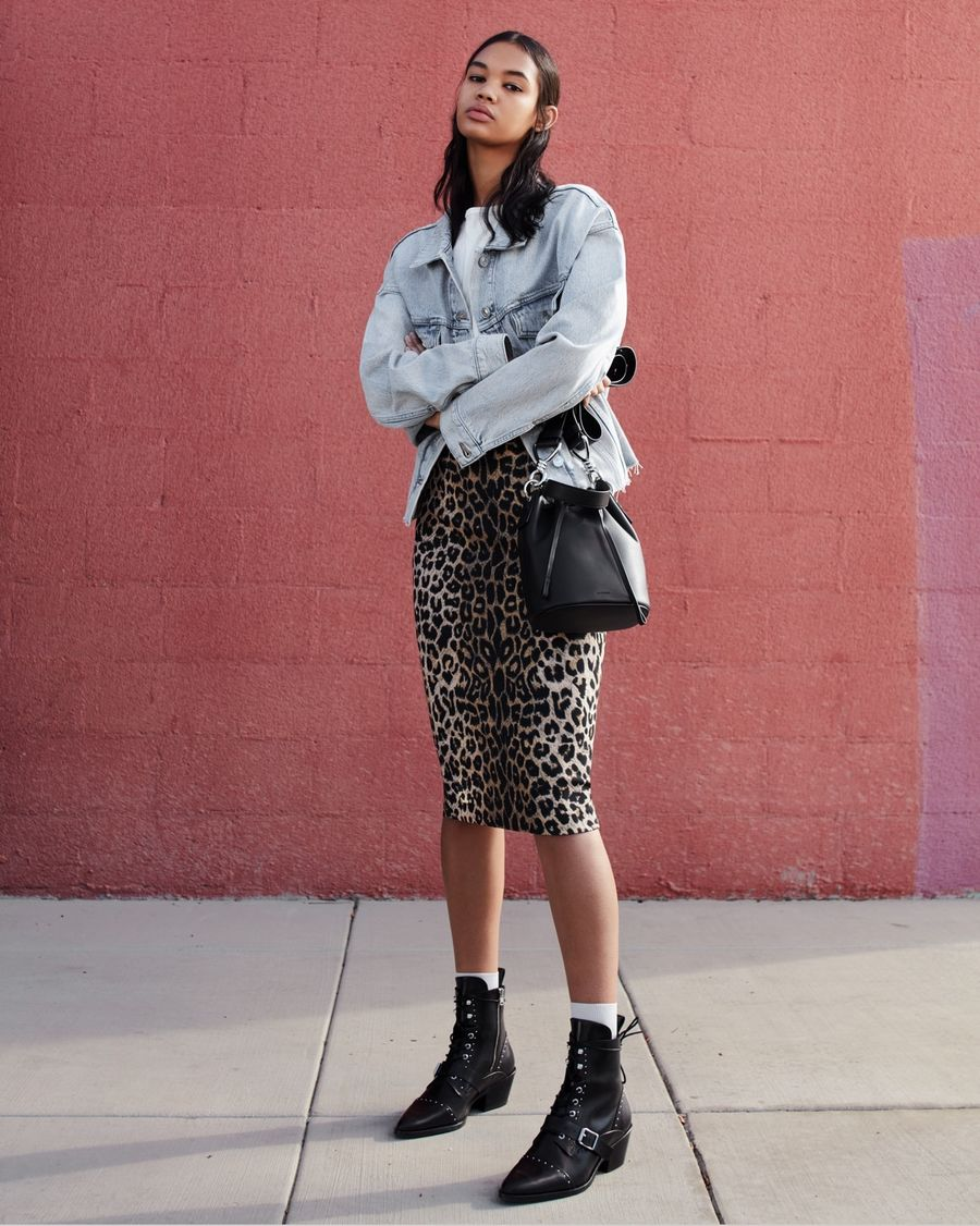 Image of a woman posing in front of a pink wall in the street and wearing a leopard print skirt with a white t-shirt, light blue denim jacket, black leather bag and black leather studded shoes.