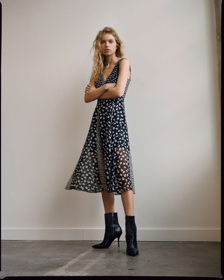 Image of a woman wearing a sleeveless black and white flower printed dress with black studded boots.