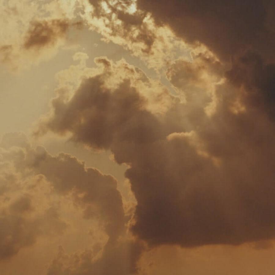Photo of the sun peaking through dark clouds.