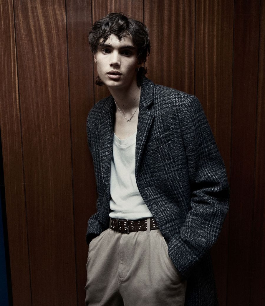Image of a man wearing a white tank top, tailored trousers and a checked coat.