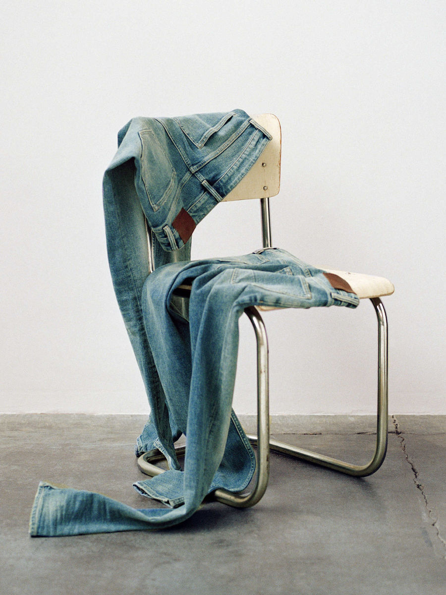 Two pairs of jeans thrown over a chair.