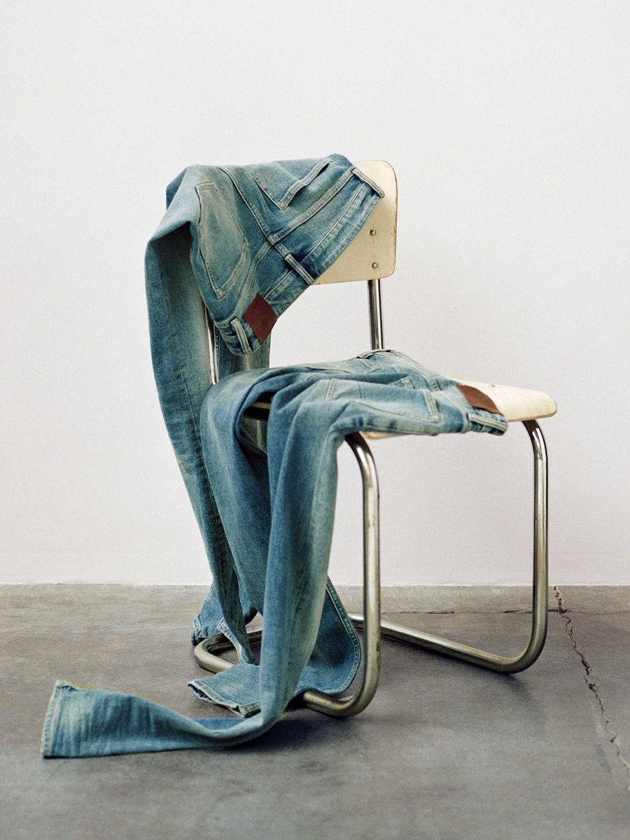 Deux paires de jeans jetés sur une chaise.