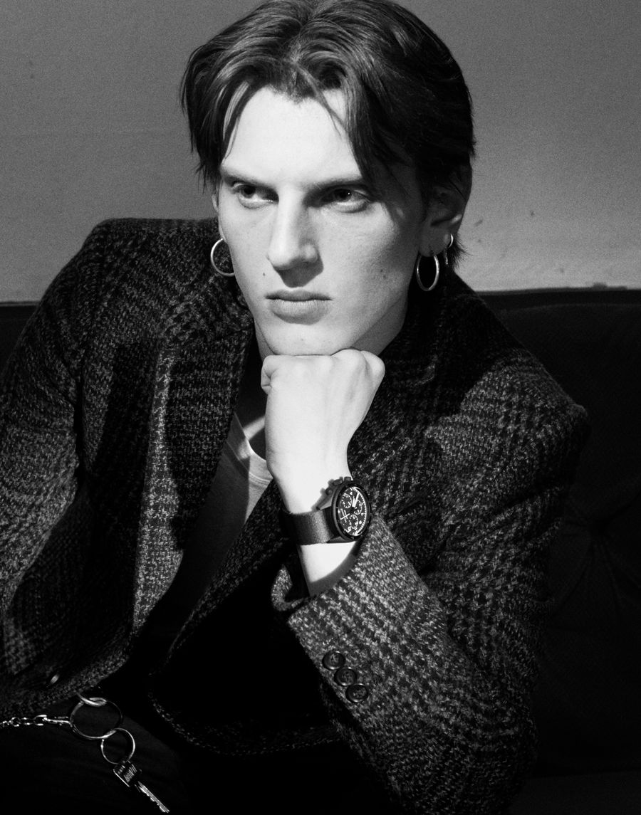 Black and white portrait of a man wearing a checked coat from our collection and showcasing one of the watches.
